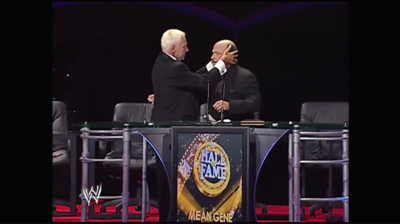 Heenan grabs Okerlund by the dome